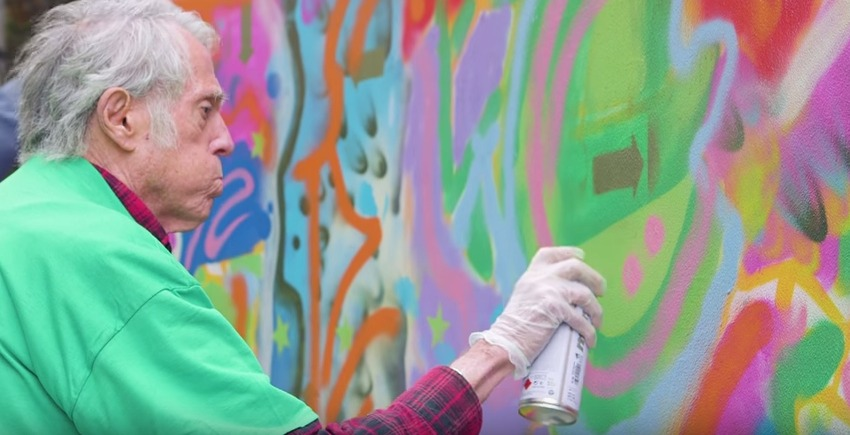 Photo of mature adult painting graffiti