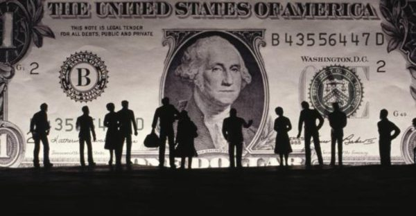 dollar bill with silhouettes of people in front of it